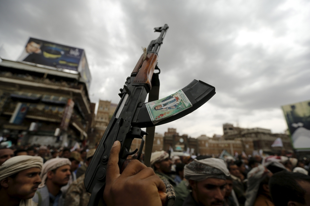 Shi'ite Muslim rebel holds up his weapon during a rally against air strikes in Sanaa